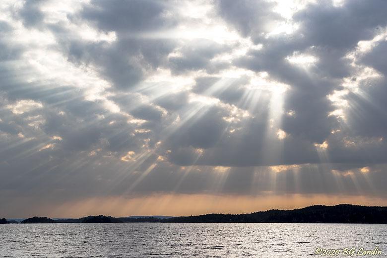 Solstrålar på kvällshimmel